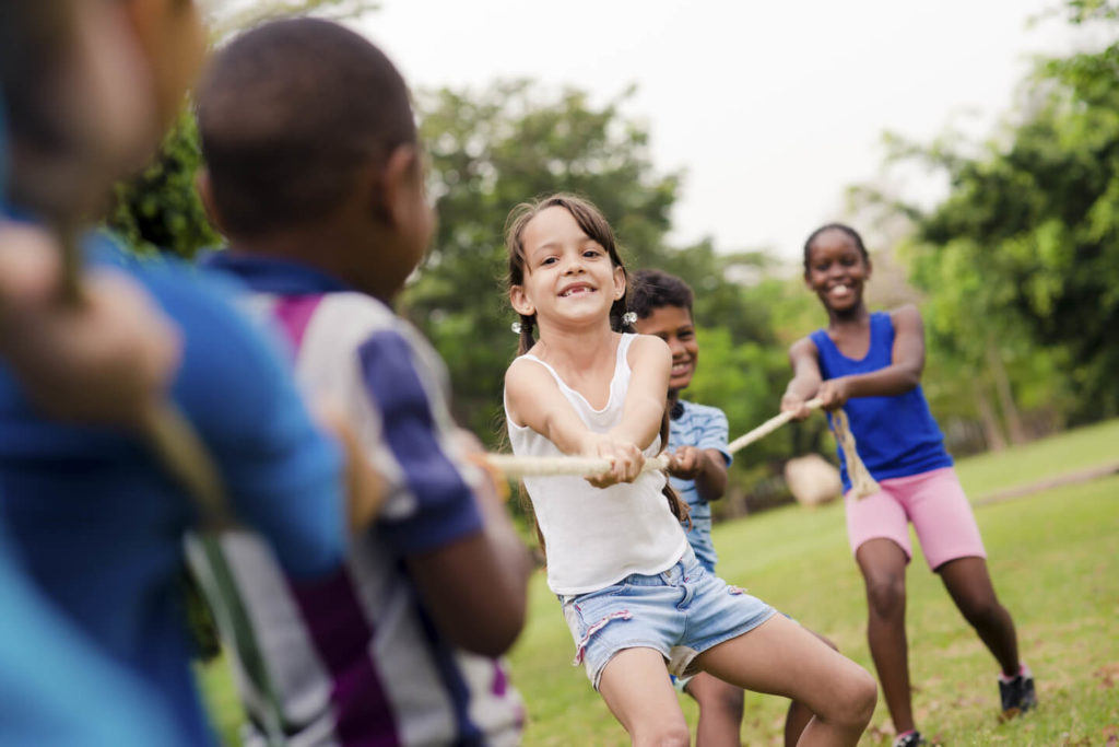 children playing at summer camp after getting off a minibus